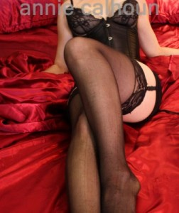 New Orleans Elite Escort Annie Calhoun : Description - A fair skinned woman wearing a black corset, black stockings, and a black garter belt with lace reclines on red satin sheets.
